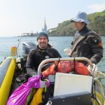 Murat driving boat under supervision of Ben