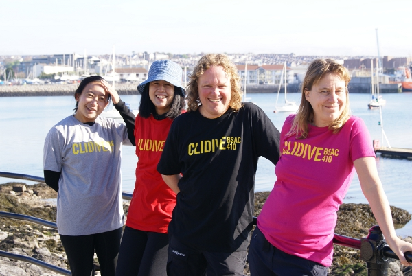 Four people wearing Clidive T-shirts