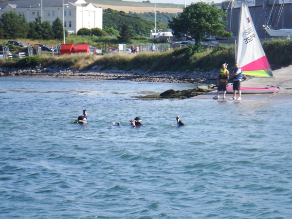 Sailors look puzzled as the students test their buoyancy at bottom of slipway